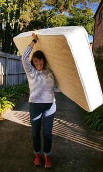 A volunteer carriers a mattress into the home of a needy person