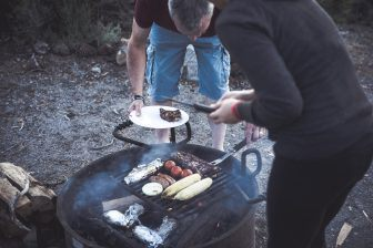 Good friends cooking up sausages at a campsite