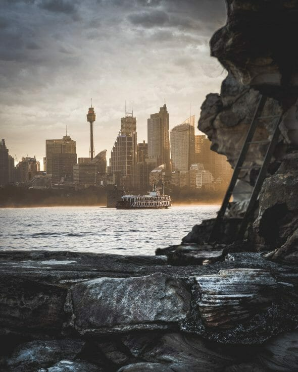 A photo by Anton Mills of light hitting a boat in from of the Sydney Skyline from Cremorne Point