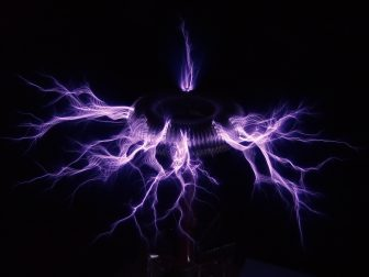 A tesla coil surrounded by purple sparks of electricity, similar to the one at the Scienceworks museum in Melbourne. Scienceworks is a good rainy day school holiday activity.