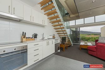 A loft apartment, looking out to the balcony. This rental unit in Bradden Canberra costs less than $500 per week.