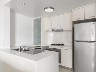 A very white and modern kitchen in a rental property in Brisbane