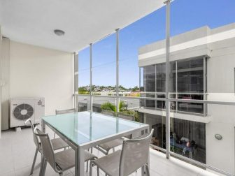 A spacious balcony with floor to wall window looks over Fortitude Valley in Queensland.