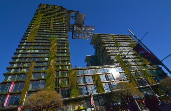 A photo from the street lookup up at the Central Park Building in Sydney, with a blue sky in the background. Central Park is covered in plants and greenery, and has a 5-star green building rating.