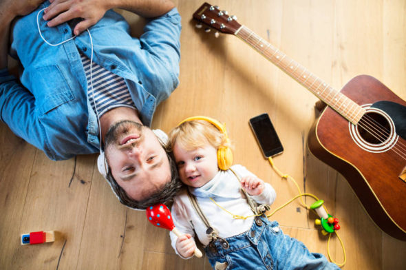 Young kid and father lying on the ground listening to a podcast for kids or music for kids on headphones next to a maraca and an acoustic guitar