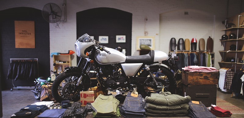 A silver Sol Invictus motorcycle sitting on top of a display box with jeans and riding wear displayed for sale