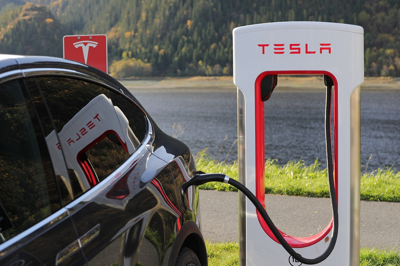 A Tesla Electric Vehicle at a charing station next to a river, with a mountain in the background