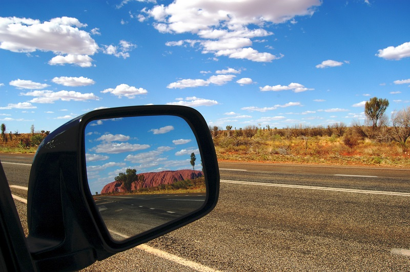 Looking out the window of a car driving in Australia, in the Australian outback, with Uluru, formerly Ayres Rock, in the rear view mirror