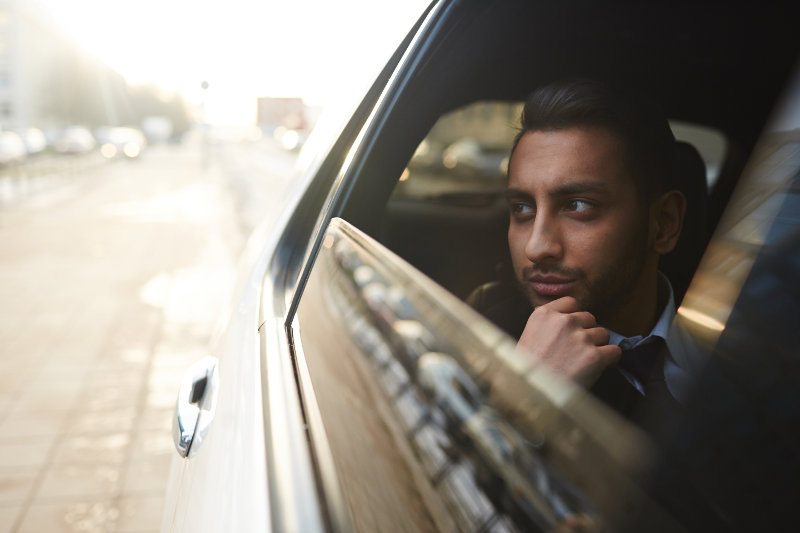Wealthy man looking through car window while traveling in the city - thanks to the selfdriving car, more people will enjoy these benefits