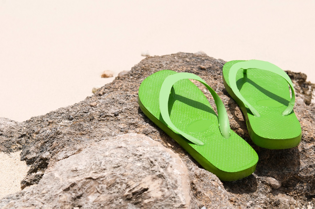 Two green thongs sitting on a rock on the sand - you don't get much traction in thongs, but is it illegal to drive in thongs