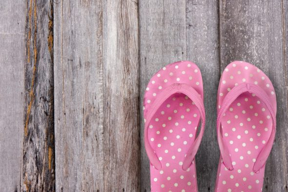 Two pink thongs on a wooden floor - you may not want to drive in thongs, but it is illegal to drive in thongs in australia
