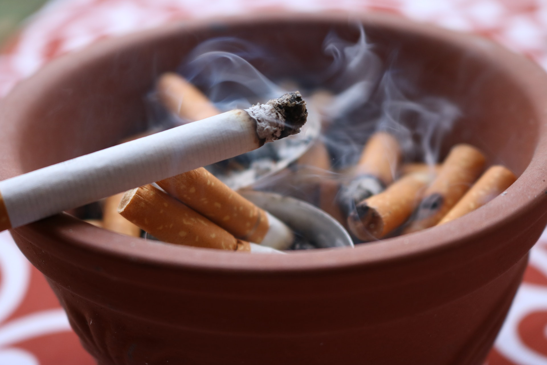 A ceramic ashtray full of cigarette butts and a lit cigarette on the edge - is it illegal to smoke in your car in australia is a question we aim to answer
