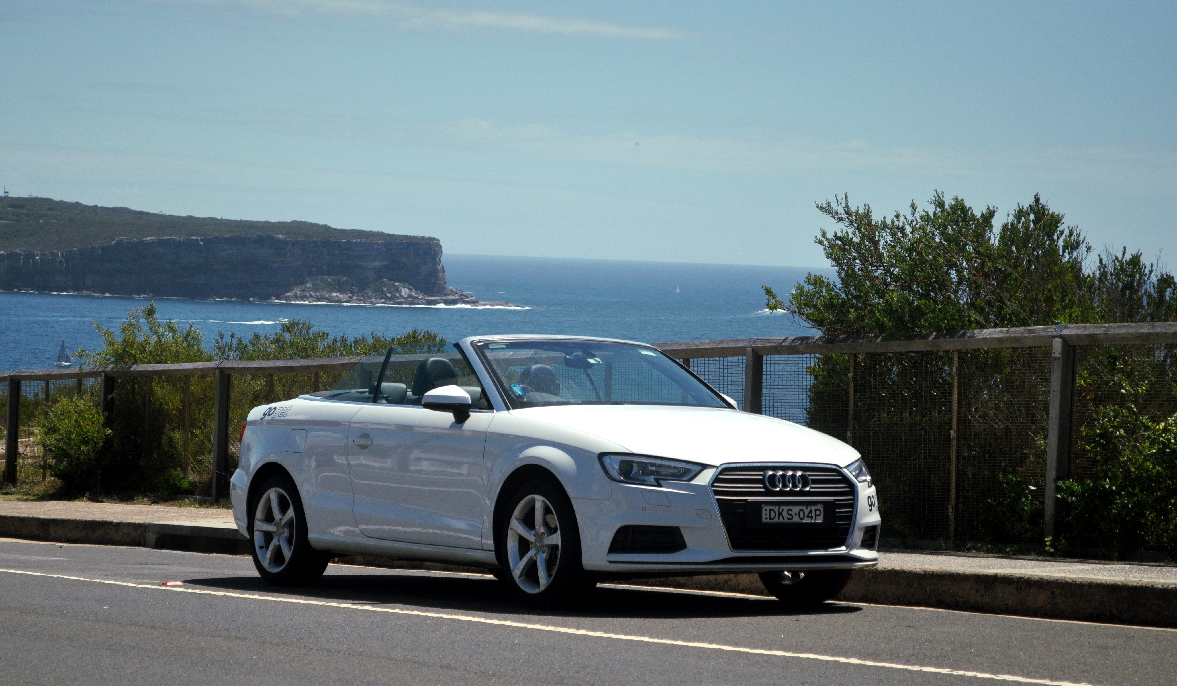 A white GoGet Audi A3 parked by the sea - the open ocean crashing against a rocky headland in the background