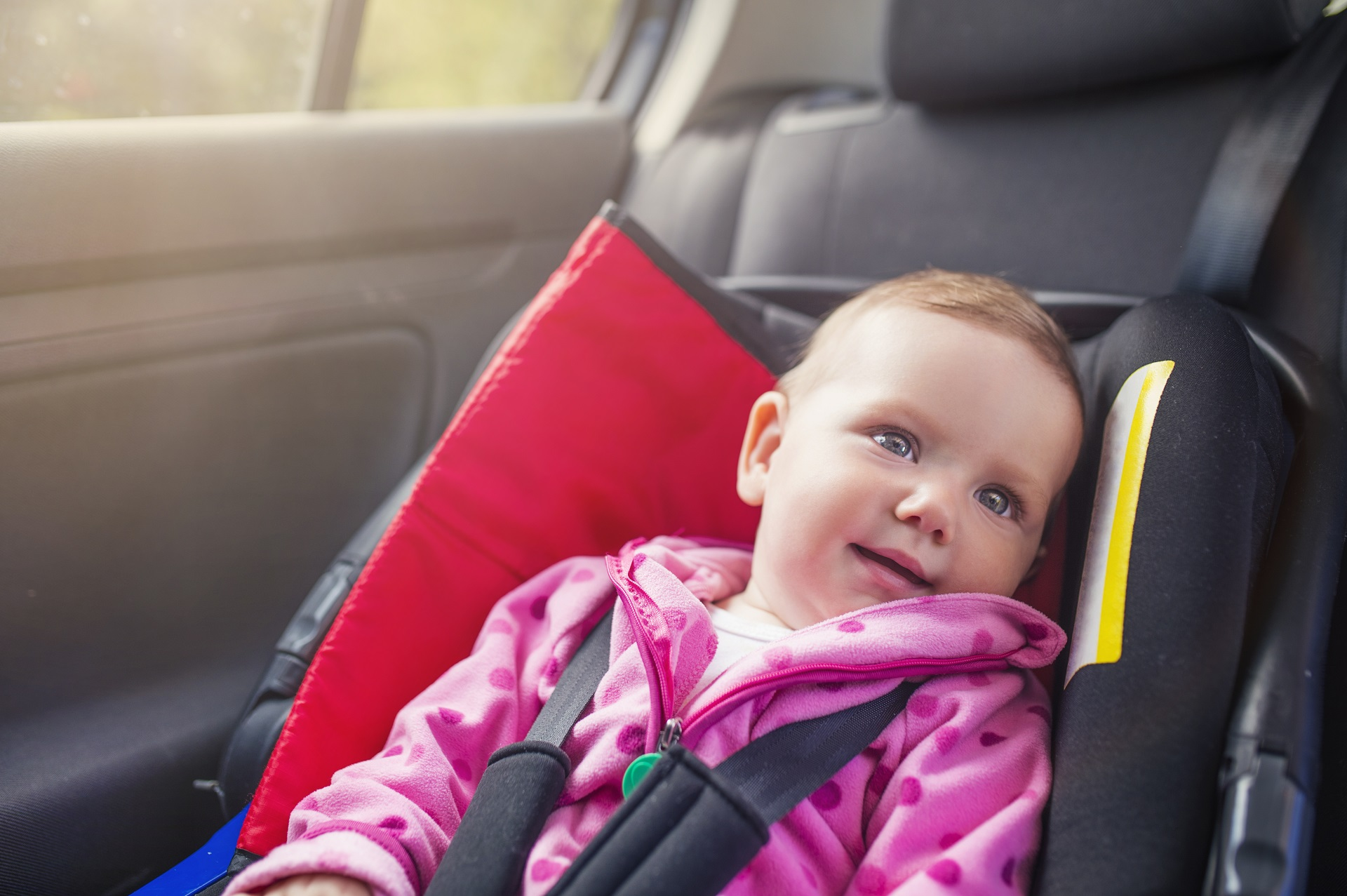 A young child in a baby seat in the back seat of a car - if you ask is it illegal to smoke in your car in australia, you should remember it's very illegal to smoke in a car when there are children