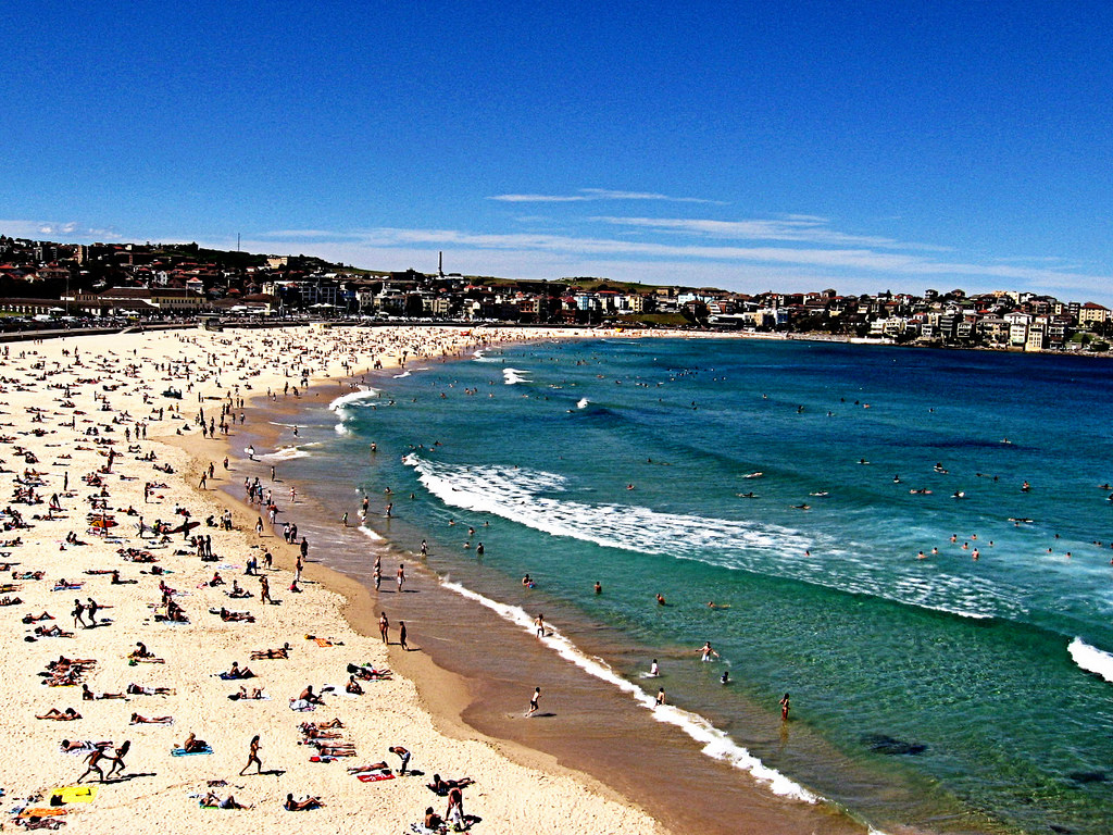 Bondi Beach on a summer's day, with lots of people on the sand and in the surf - Bondi Beach parking is hard even in winter