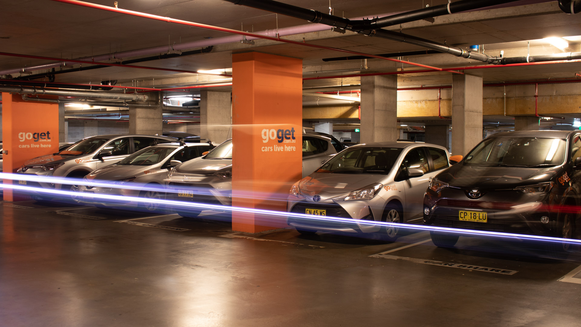 A lineup of GoGet cars in a city building car park - GoGet cars are found in car parks in Brisbane, Sydney, and Melbourne, and help reduce the competition for parking in the city