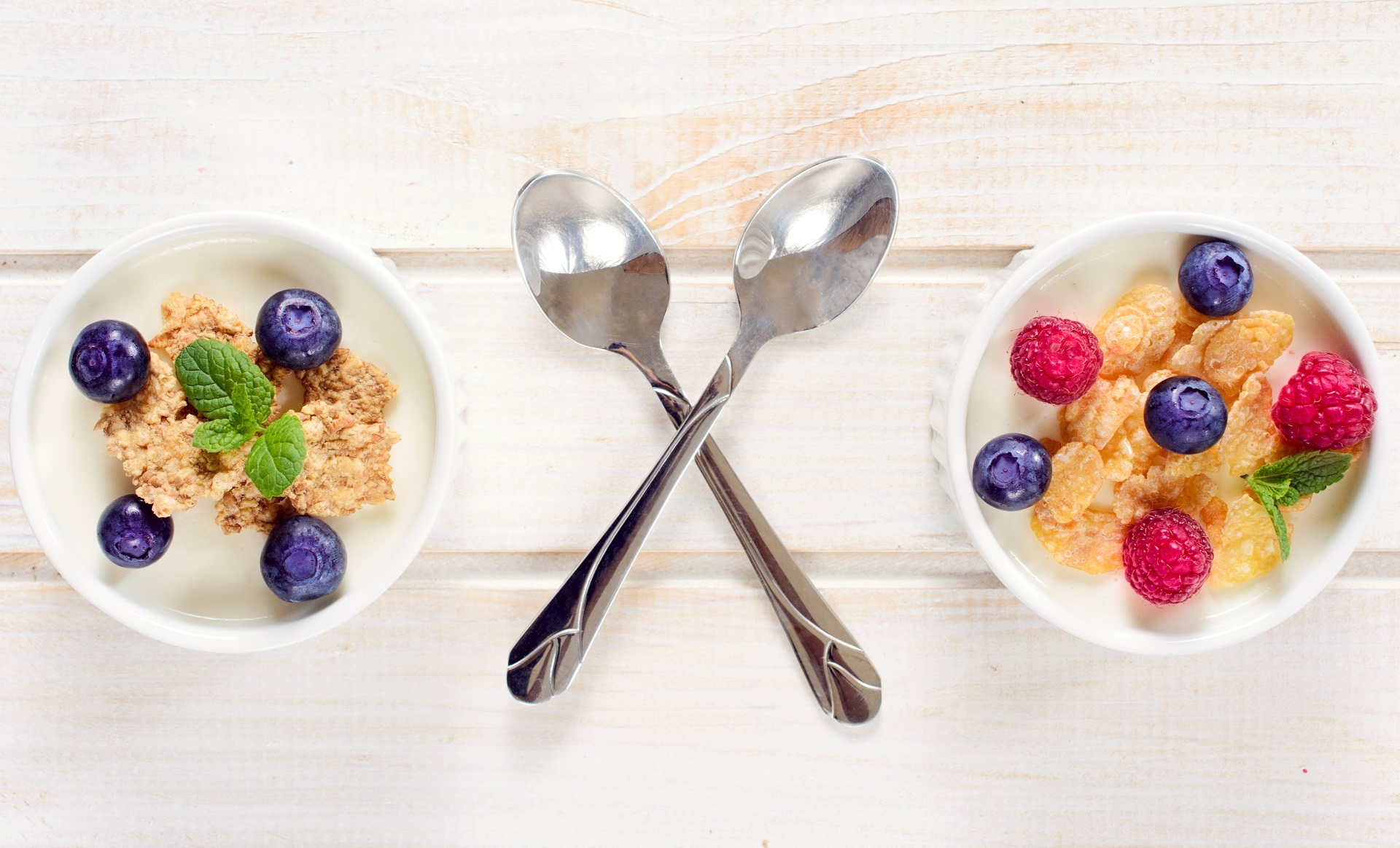 Two bowls of cereal with fruit, seperated by crossed spoons - cereal tastes great, but is it illegal to eat while driving australia