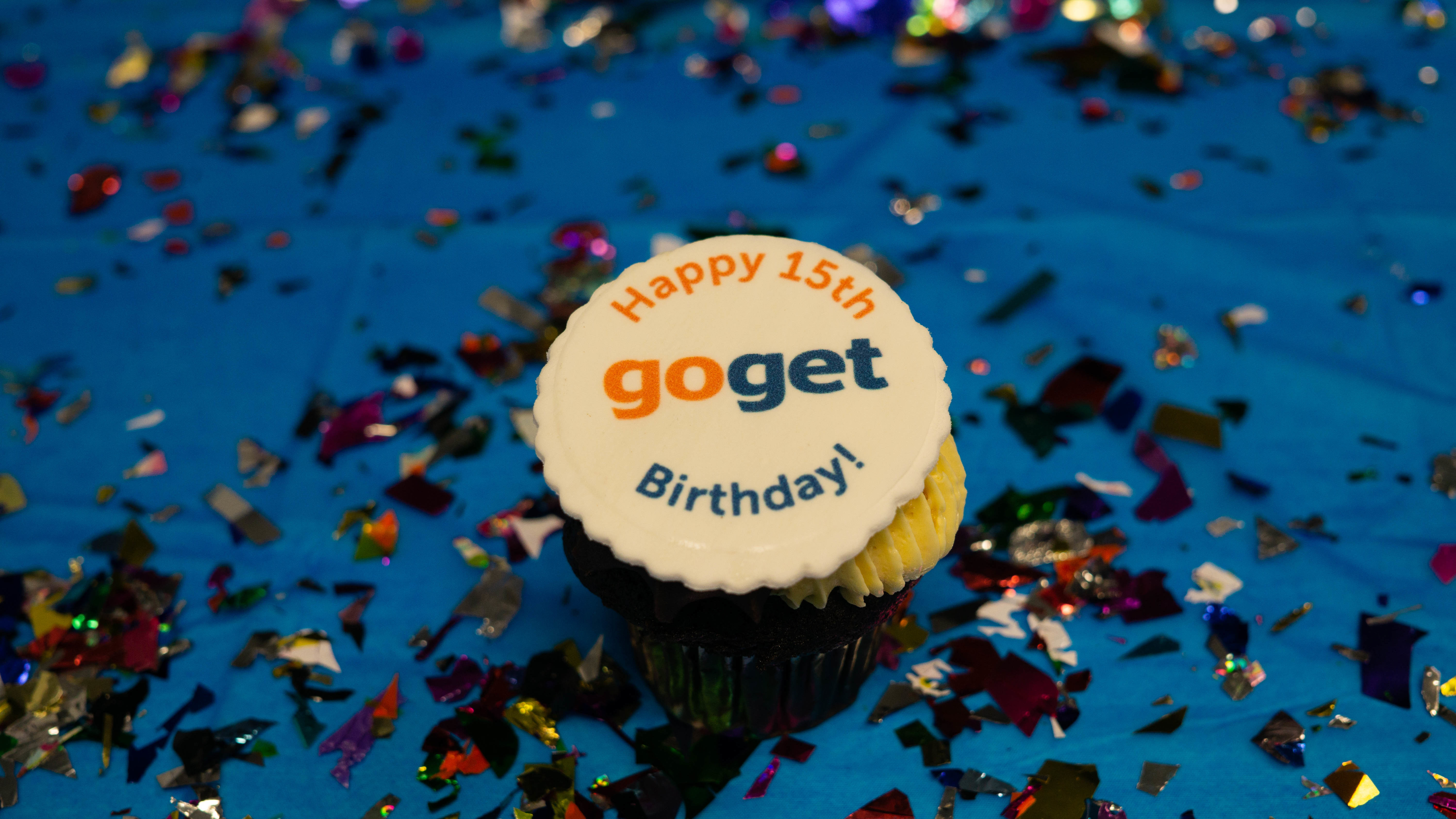 A cupcake with printed icing saying Happy 15th birthday GoGet on a a blue table covered in glitter