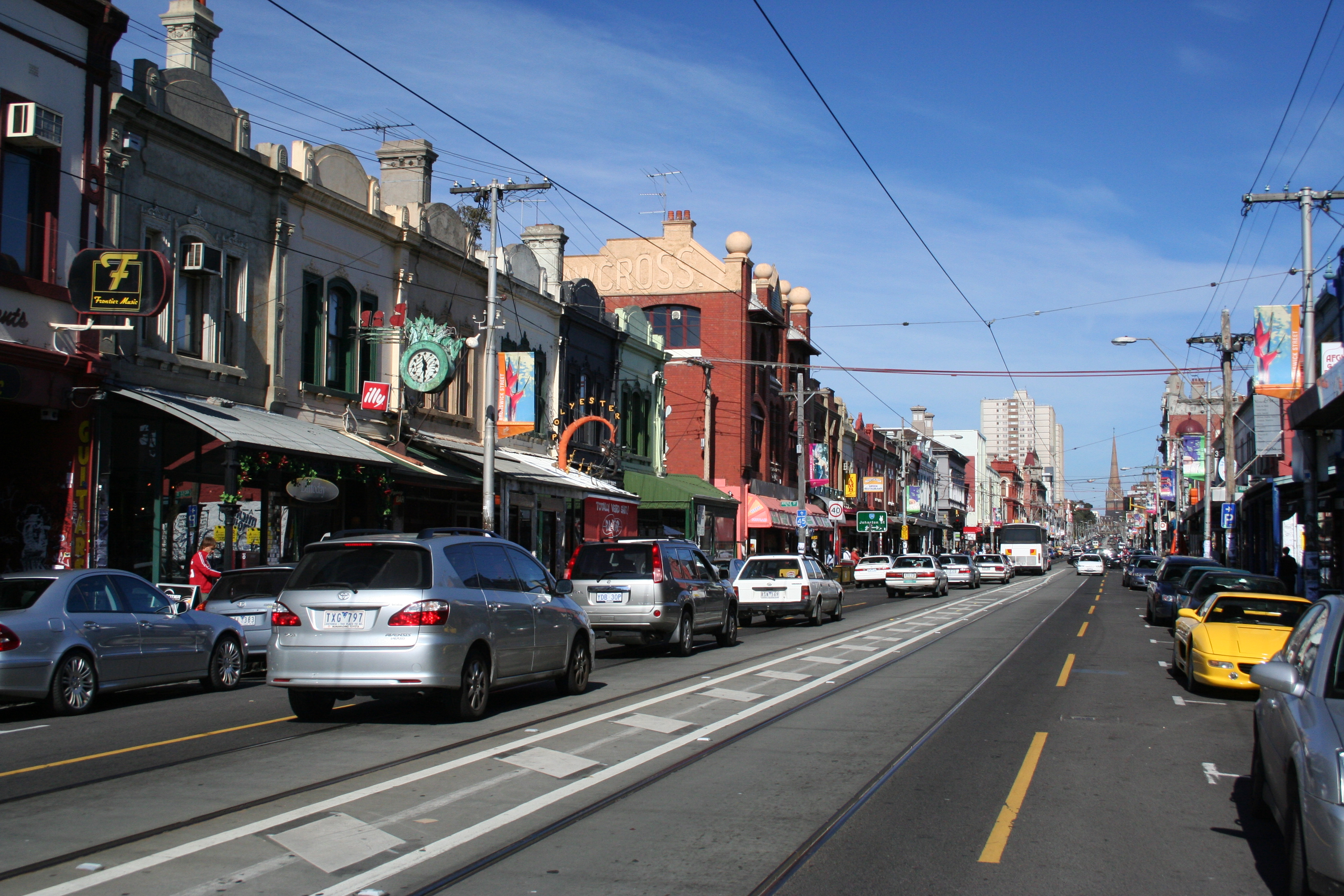 Brunswick Street in Fitzroy Australia on a sunny day, with Fitzroy parking spots filled with cars