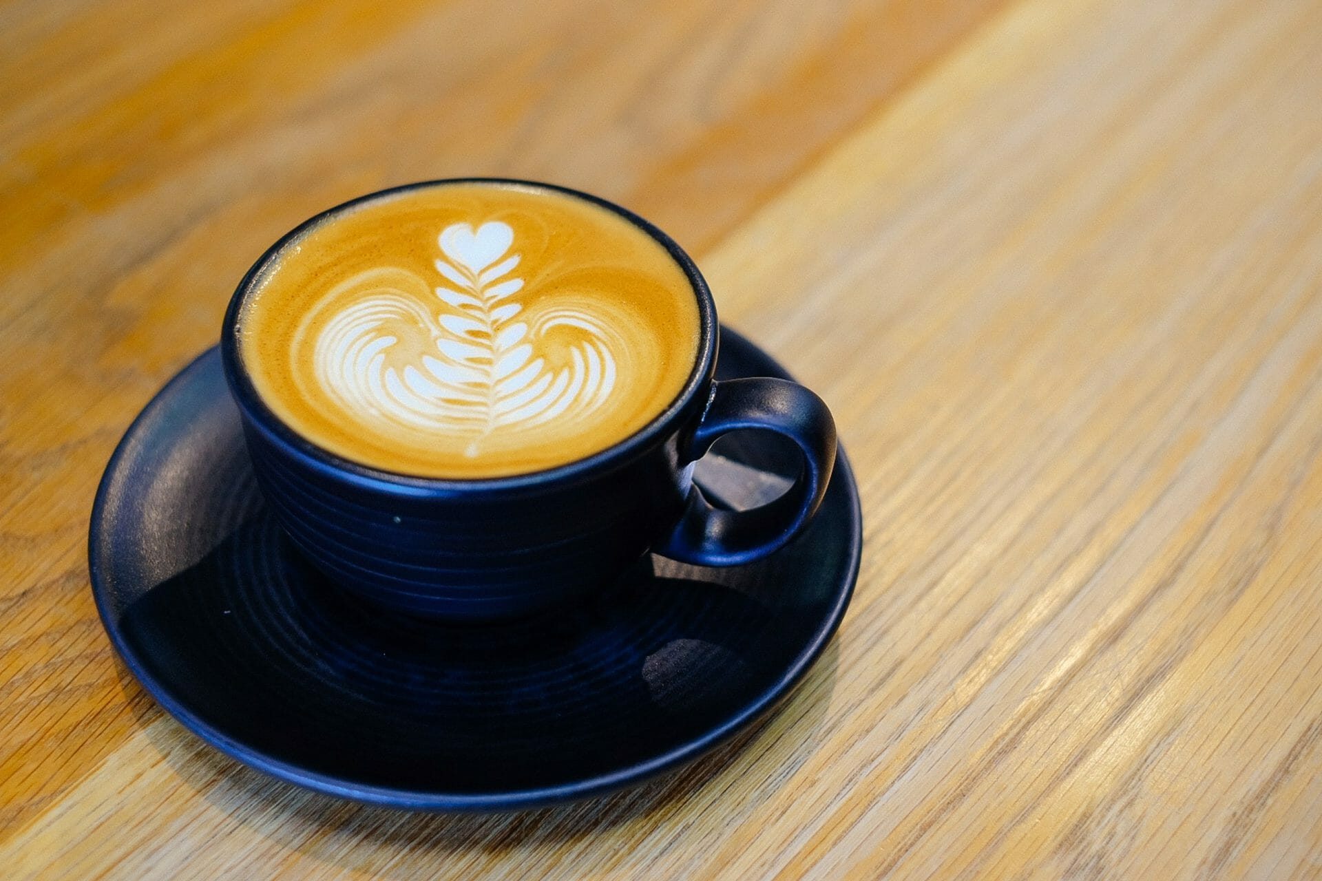 An cappuccino with decorative milk on a wooden table top at a cafe in Fitzroy, Victoria, Australia