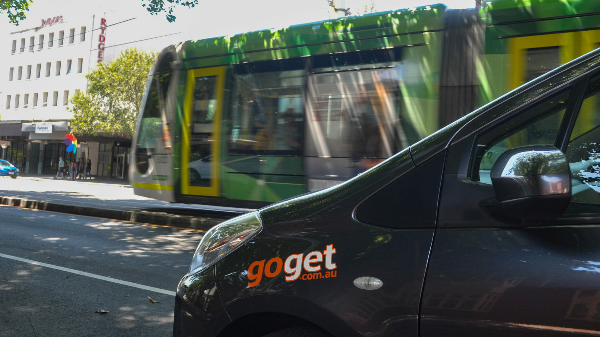 The side of a parked GoGet car share vehicle, with a moving Melbourne tram in the background