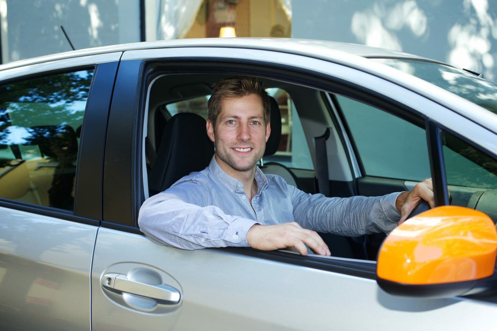 A well dressed man in the front of a GoGet car with the orange wing mirror visible - is it illegal to drive without a side mirror