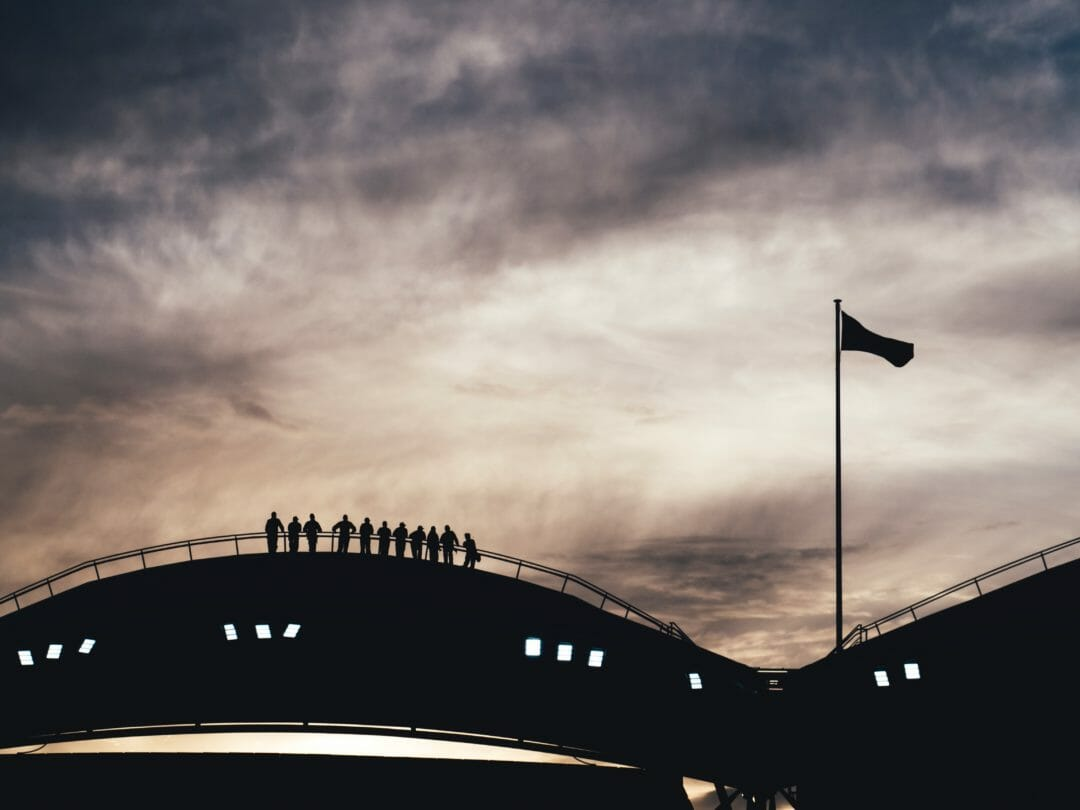 The silhouette of a dozen climbers on the top of one of the sails of Adelaide oval, moving along it at twilight