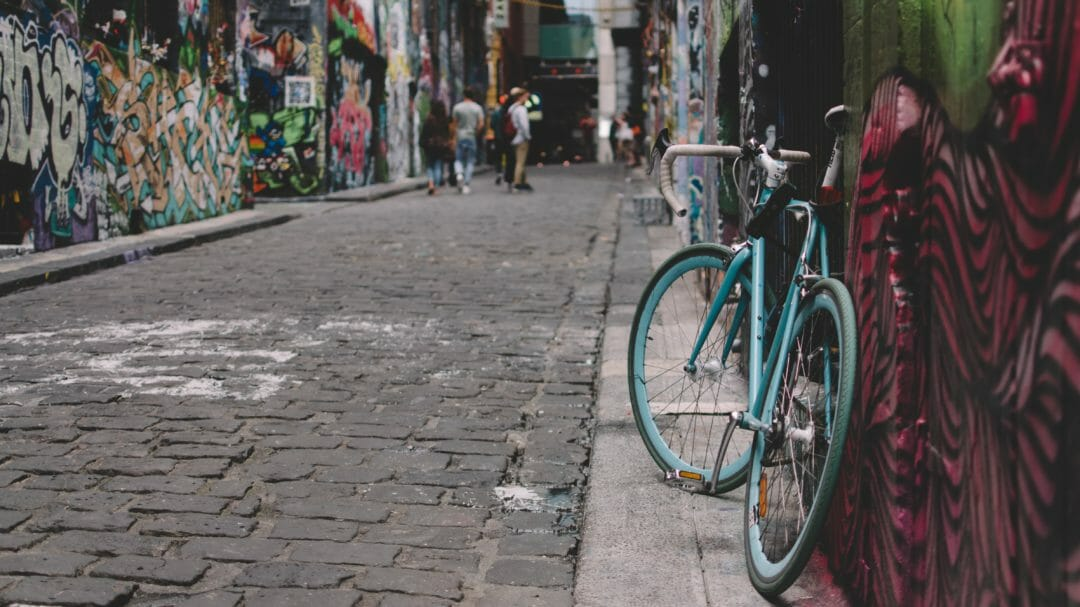 A bike propped up against a wall in a Melbourne laneway, with graffiti on the walls - parking in Melbourne is made easier when locals ride more than drive
