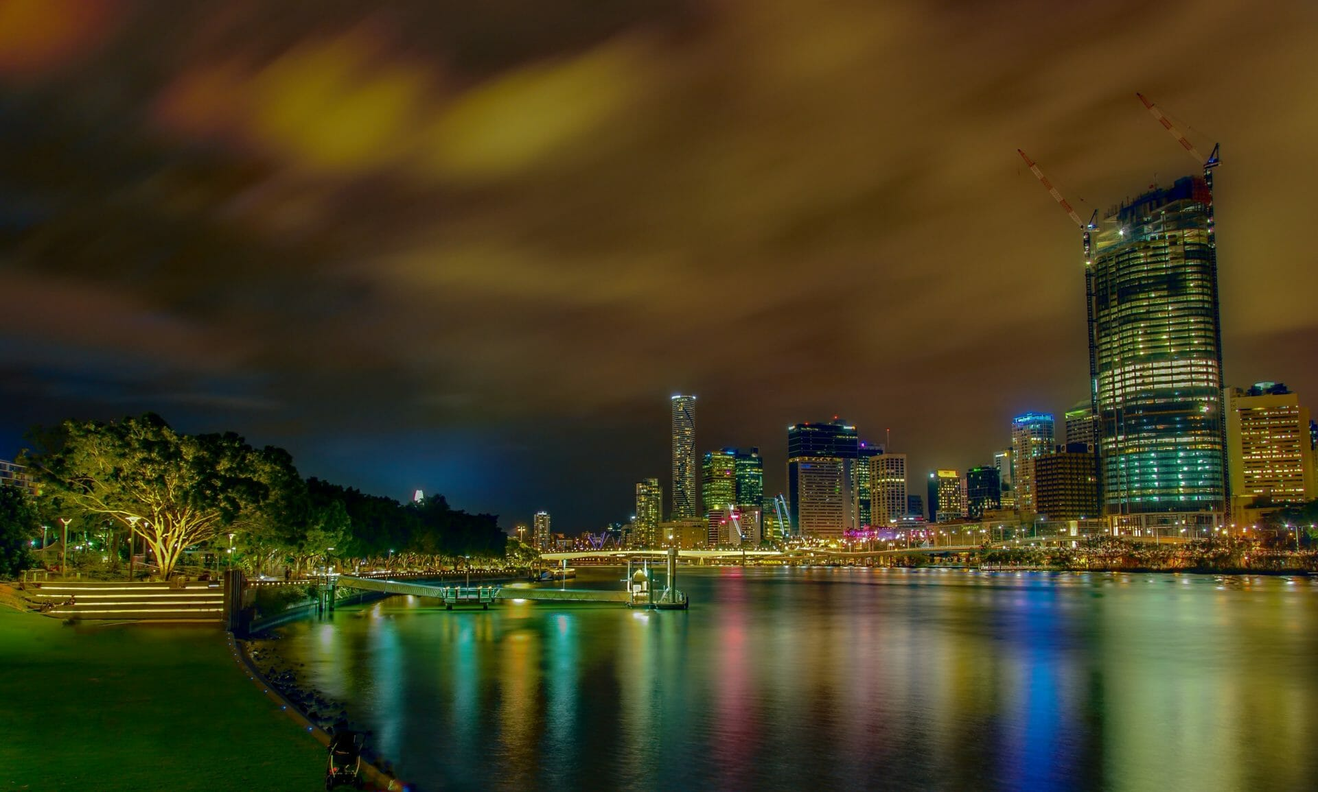 The Brisbane skyline over the Brisbane River at night, with vibrant colours you'll often see when moving to Brisbane
