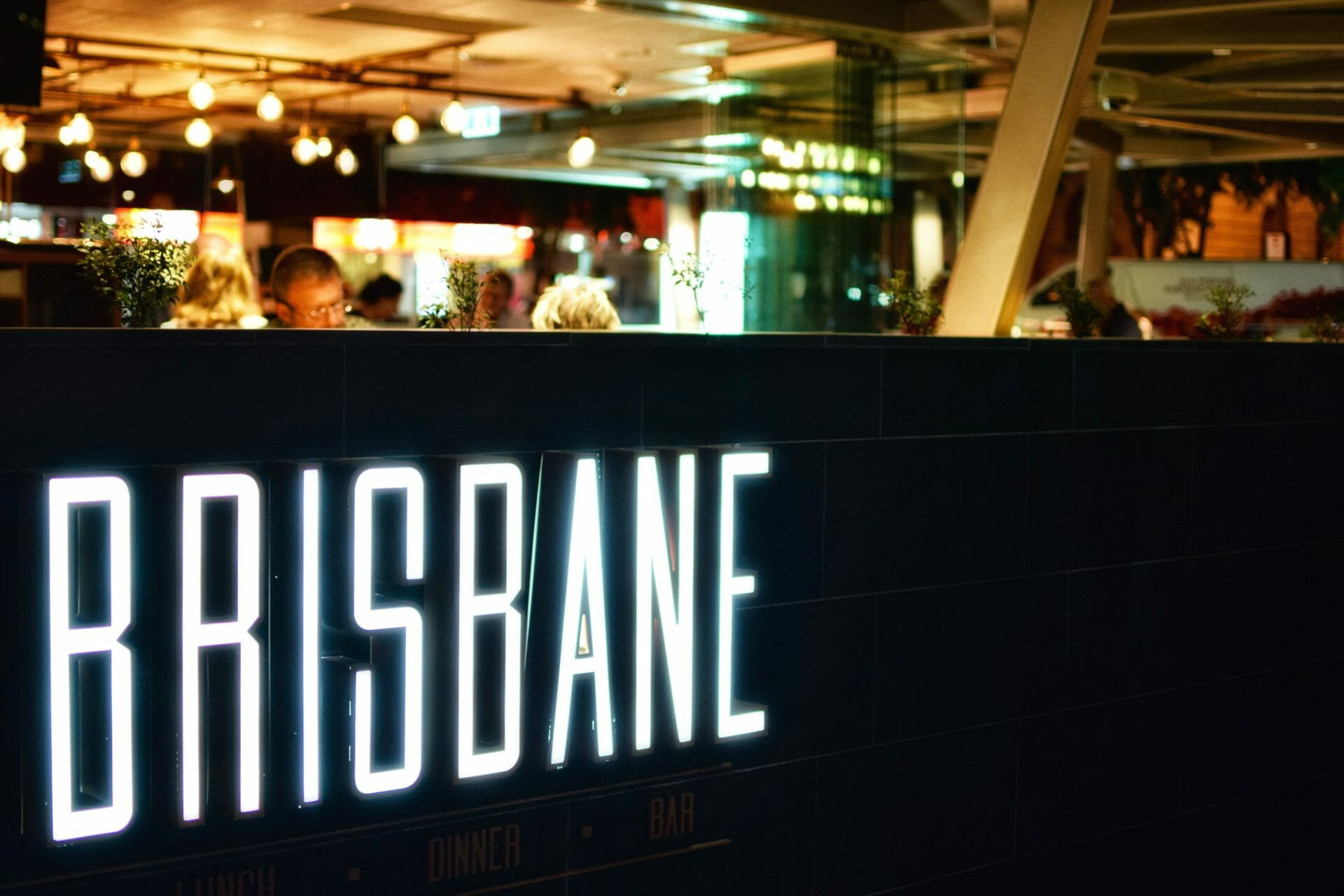 A busy restaurant in Brisbane Australia, with a light up sign that says Brisbane - a common sight when moving to Brisbane