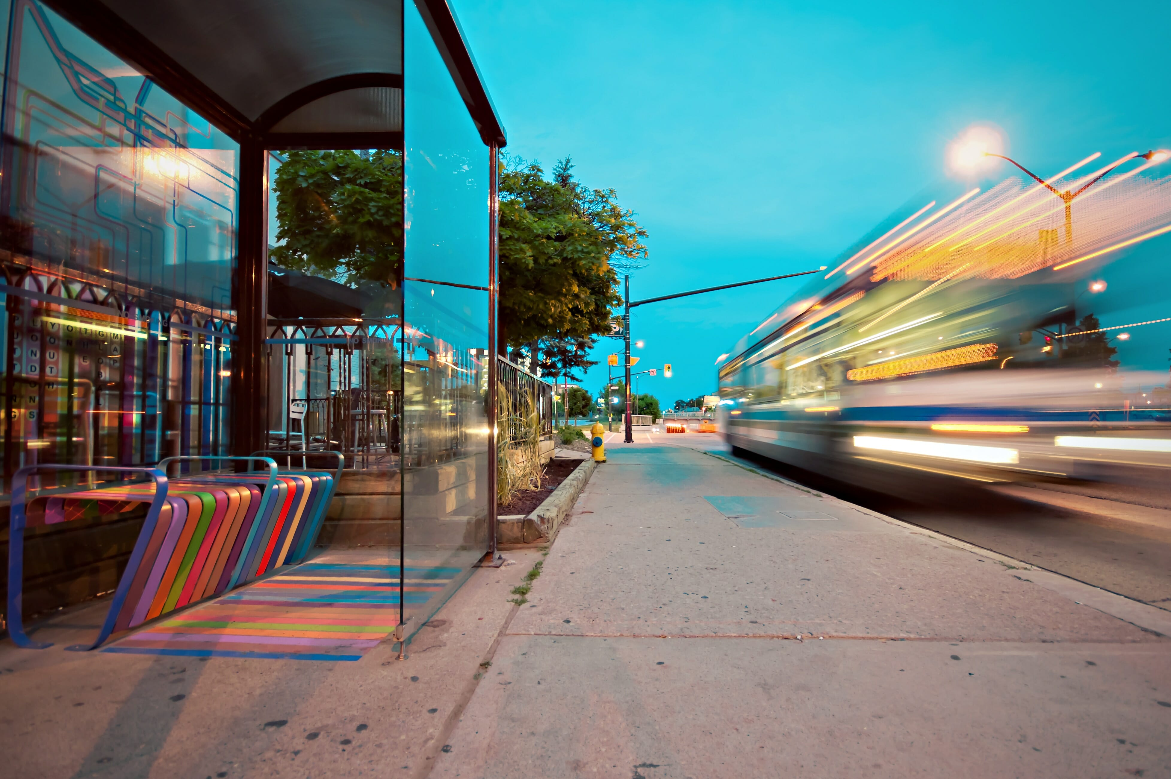 A long exposure of a bus driving past a glass bus stop on its way to Brisbane airport