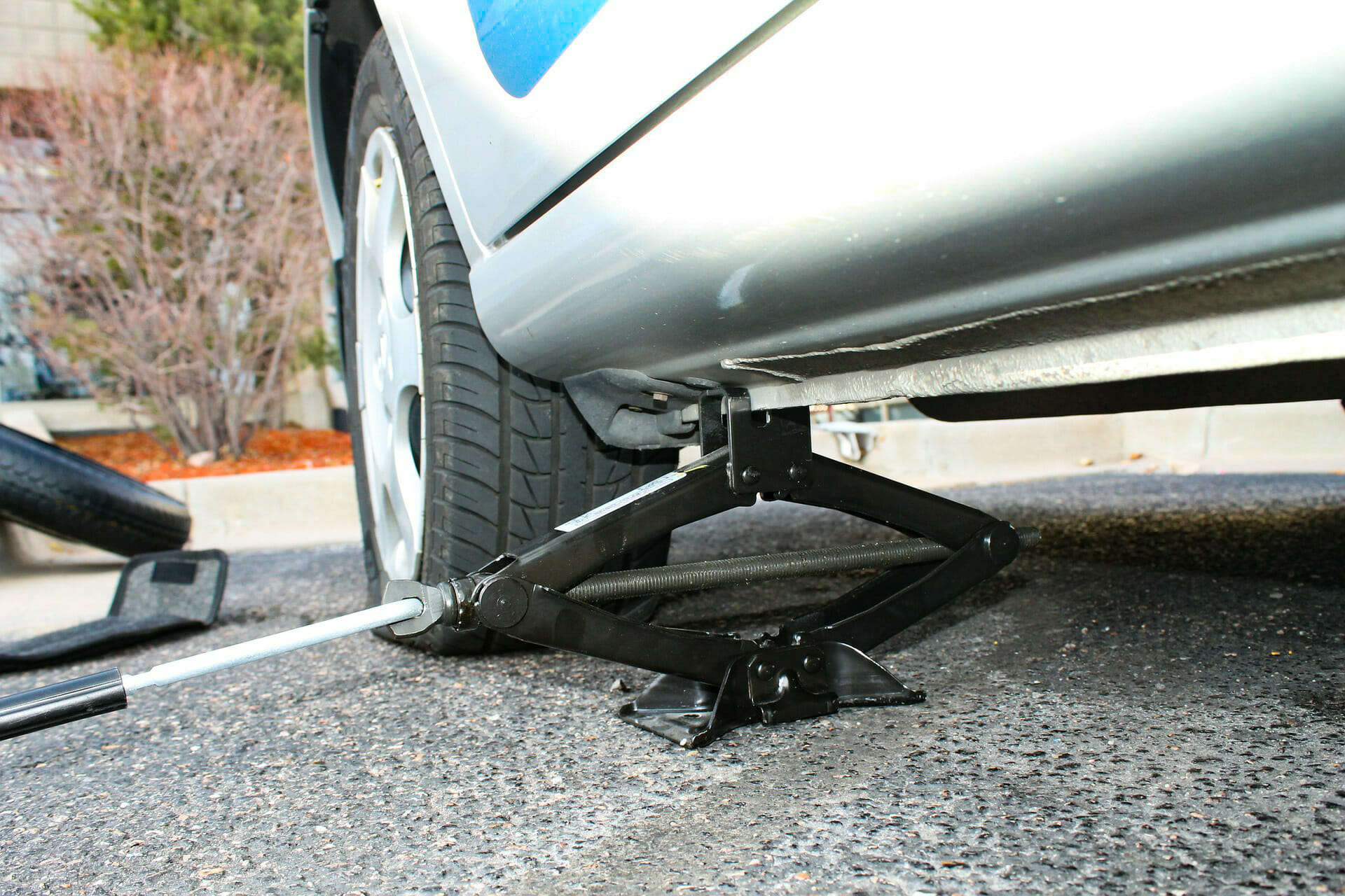 A car with a flat tyre on a jack - someone is about the change a tyre on this car - How to change a tyre