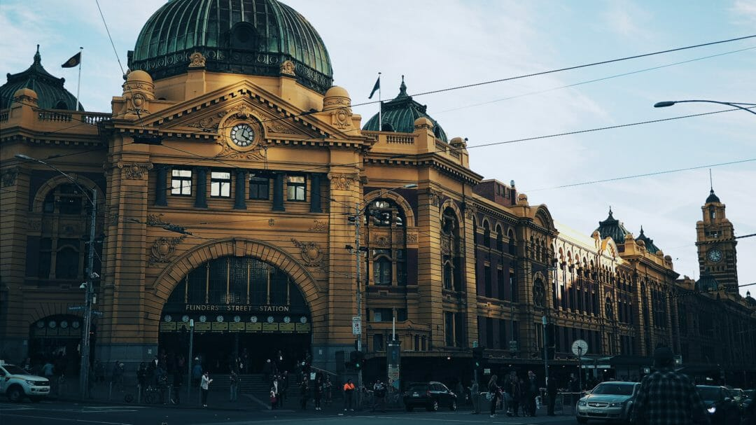 Flinders street station in Melbourne city, with cars drive past on the road, where there is no Melbourne Parking available