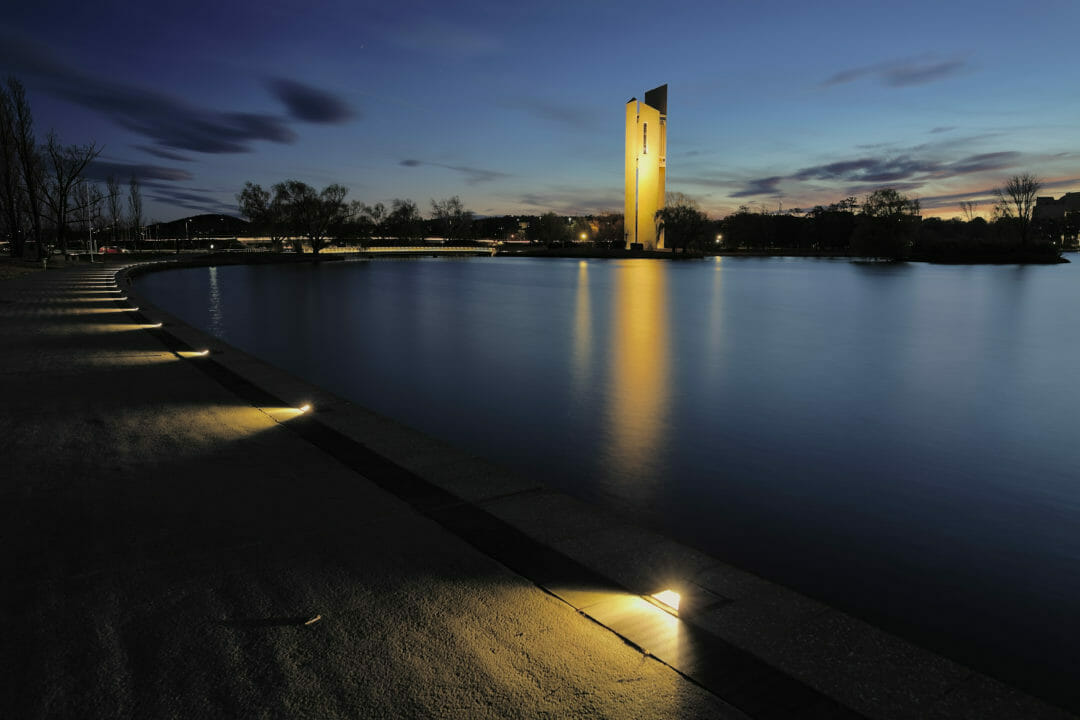A night time shot of Lake Burley Griffin at night, with the monument lit up from below