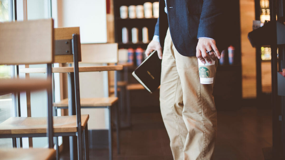A man in a Melbourne Starbucks carrying a book to his table