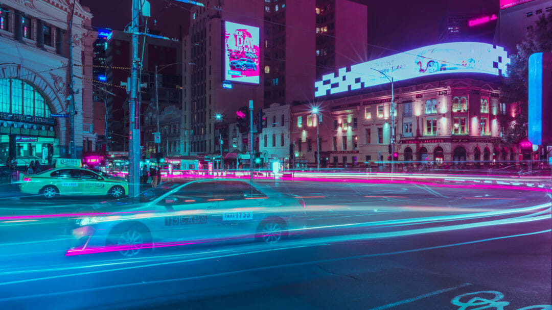 A long exposure image of Melbourne Streets at night, with a taxi racing past