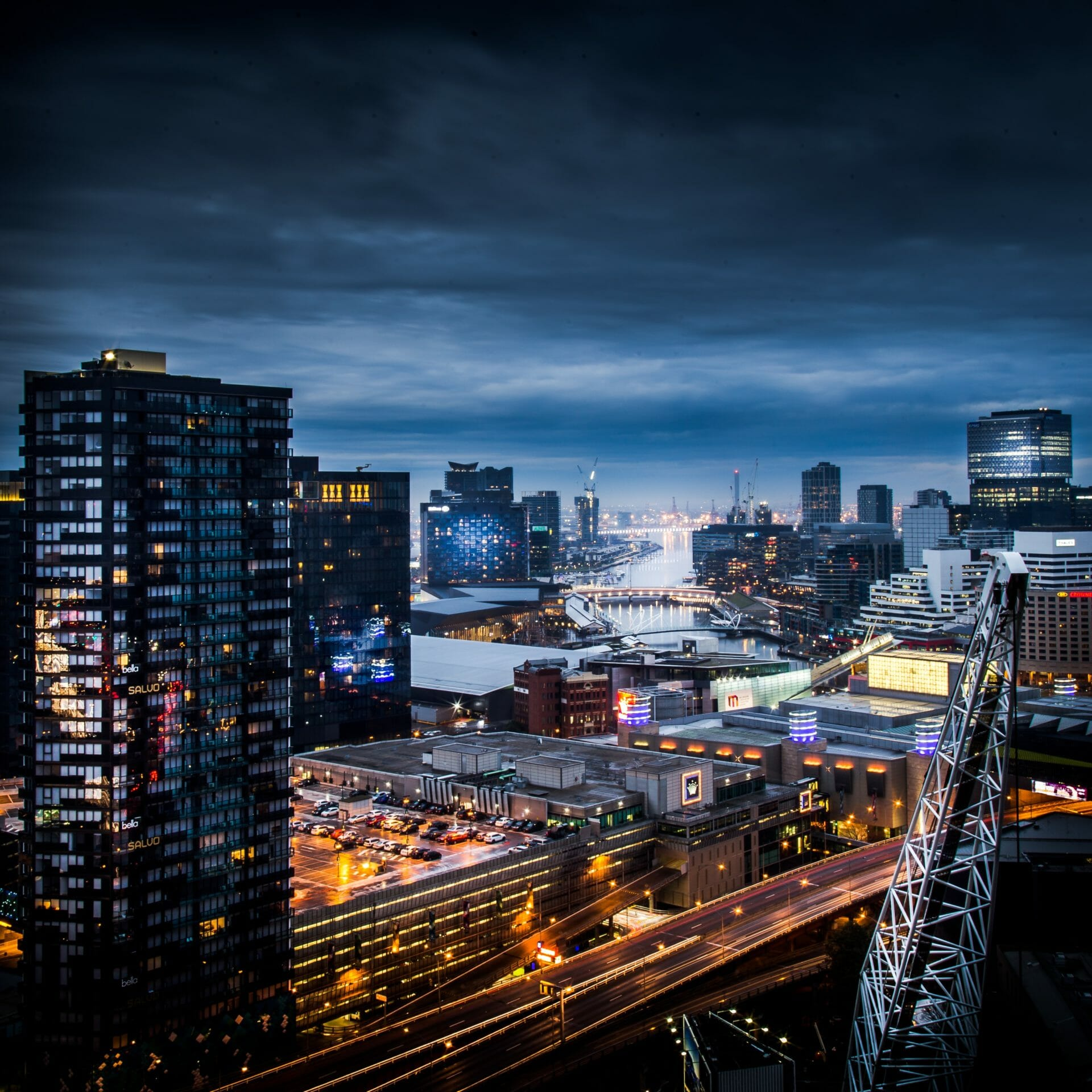 A dramatic night time view of the Melbourne CBD with moody cloudy overhead
