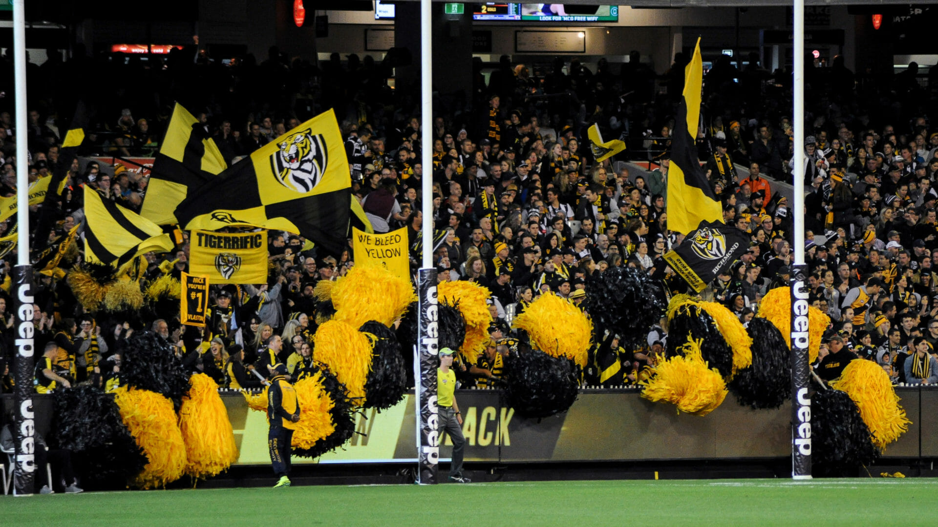 AFL fans of Richmond parked behind the goal posts of the Melbourne Cricket Ground waving yellow and black colours