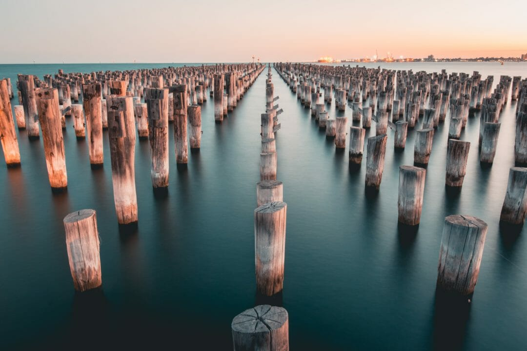 A grid of Jetty struts coming out of the water at St Kilda, with Port Melbourne on the horizon - Moving to Melbourne you could do worse than St Kilda.