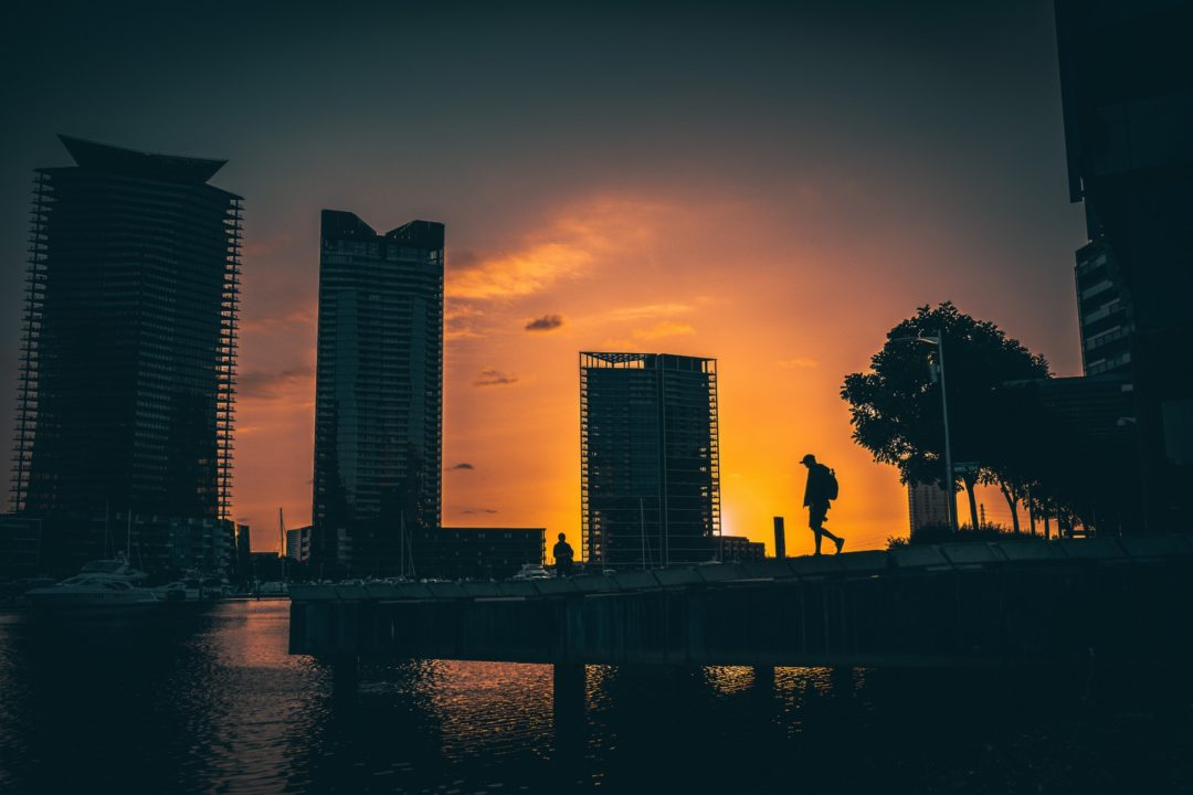 The silhouette of a man walking in Docklands at sunset - Moving to Melbourne means you can look forward to sunsets like this
