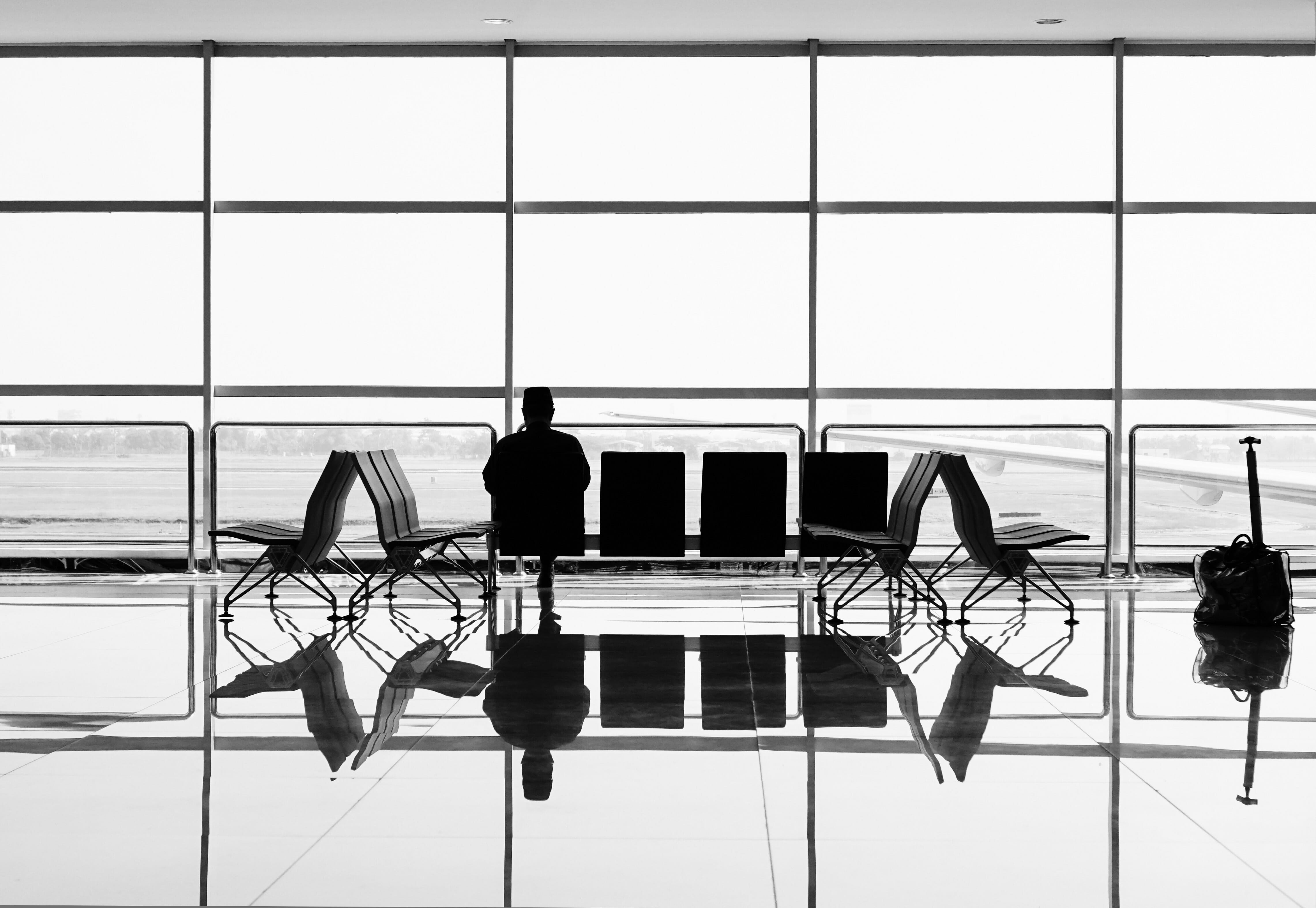 Black and White image of a man waiting at an airport in Adelaide Free Wifi on his phone