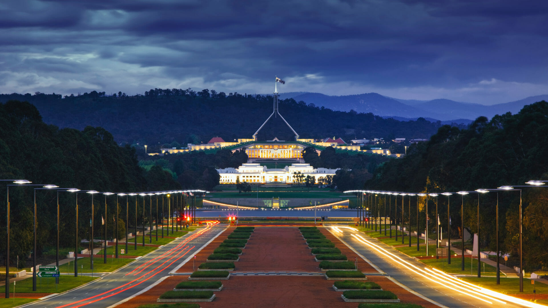 Federation mall at night time, with Parliament House in Canberra at the end
