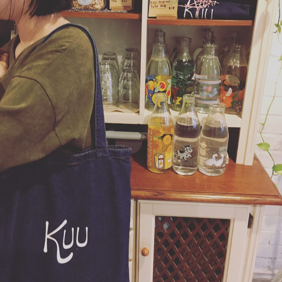 An Interior view of Kuu Japanese cafe in Melbourne, with a young woman wearing a Kuu tote bag