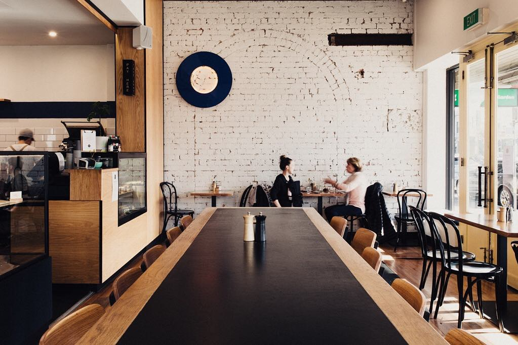 An interior shot featuring a long central table at Mayday cafe in Melbourne, one of the best Melbourne cafes according to GoGet members