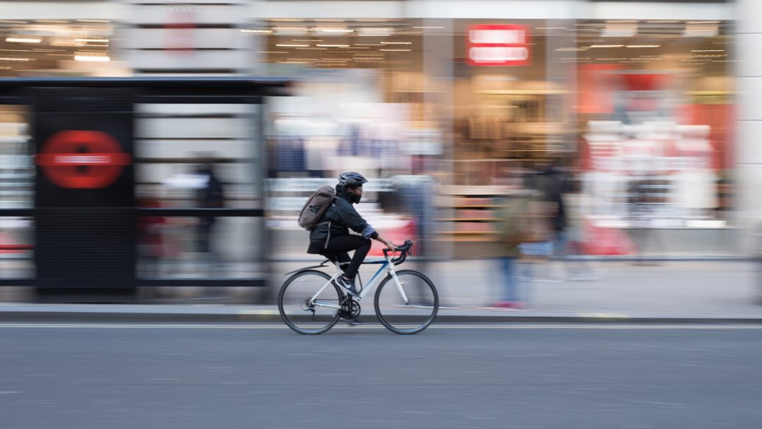 A rolling shot of a man riding a bicycle through the city