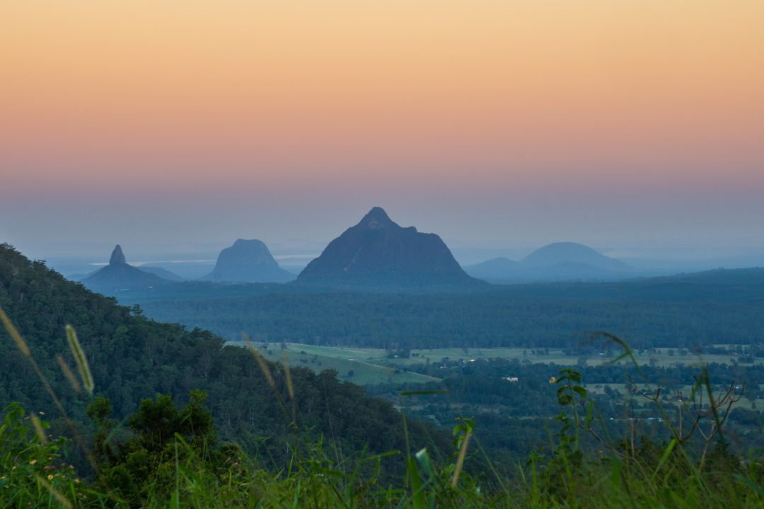 Sunset over the glasshouse mountains, viewed from the Blackhall Tourist Drive near Maleny, a great road trip for couples
