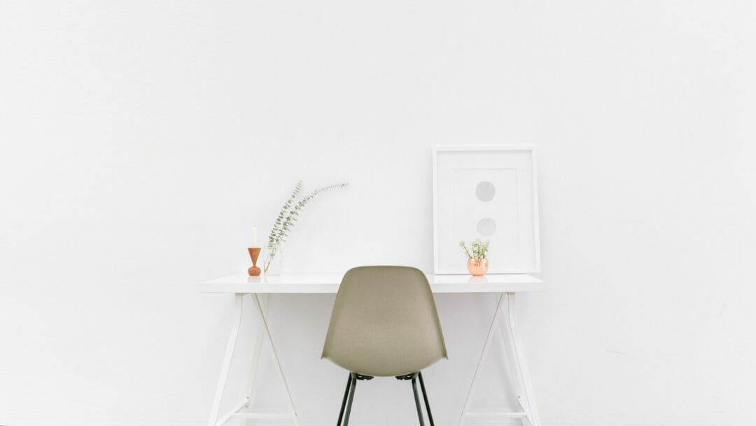 A desk in a minimalist home with a white wall