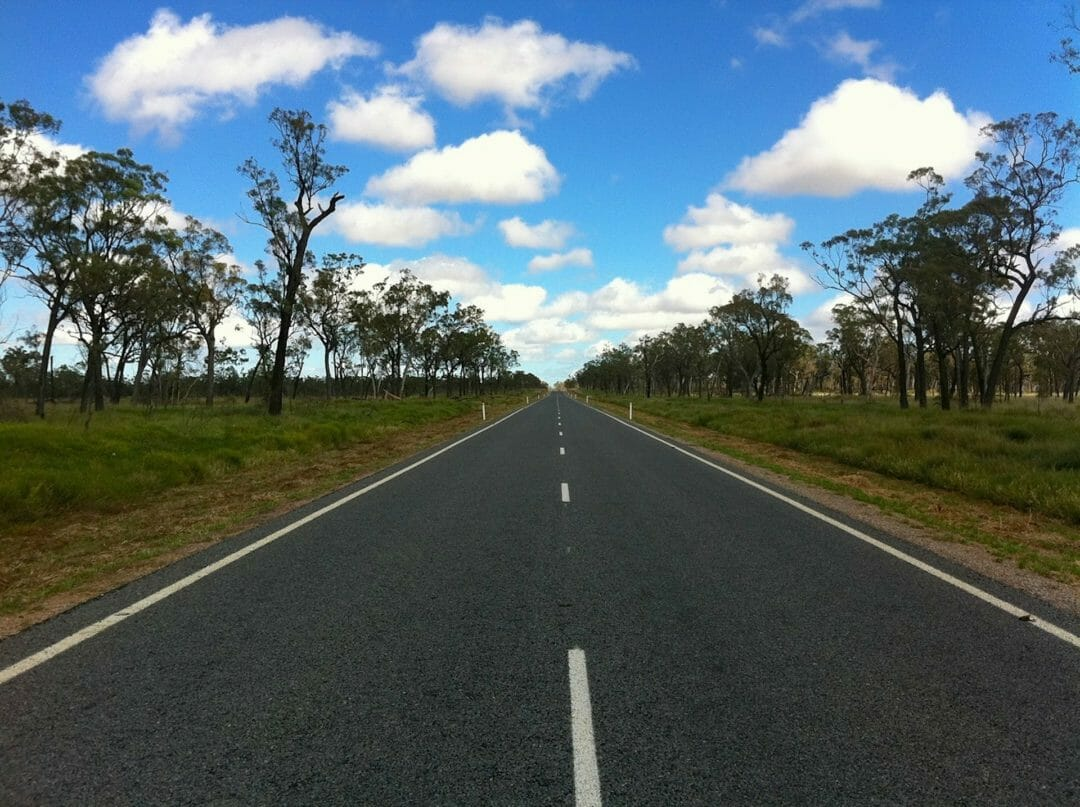 A wide open country road in Australia, with gum trees and blue sky
