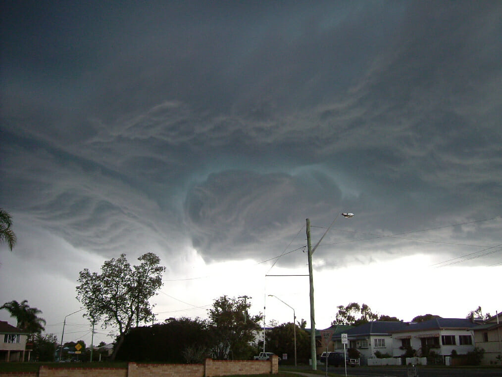 A storm looming over Brunswick Heads in Australia, with houses, roads, and cars below
