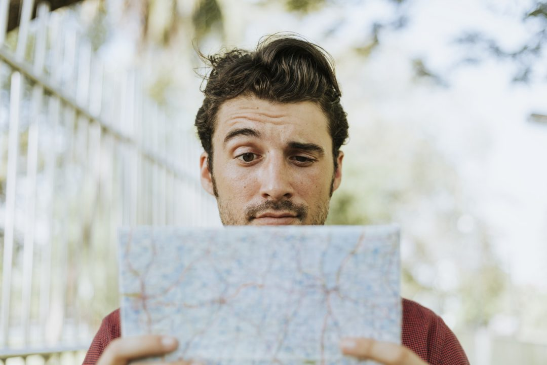 A man looking at a map with one eyebrow up before he drive in the country